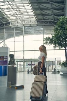 Mulher atenta mantendo a bagagem na mão esquerda enquanto está no aeroporto, em posição de semi-posição