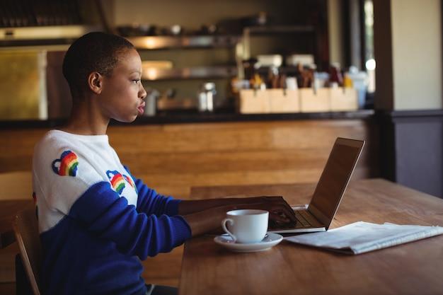 Mulher atenta usando laptop enquanto toma café