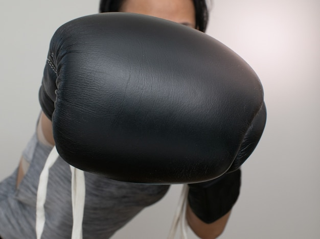 Mulher atira um soco com luva de boxe preta