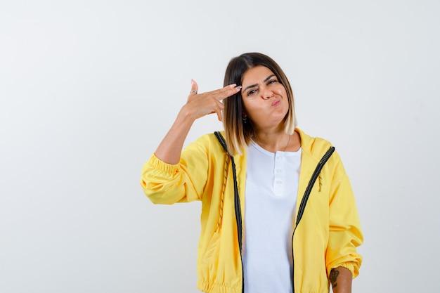 Mulher atirando em si mesma com arma de mão em t-shirt, jaqueta e parecendo hesitante, vista frontal.