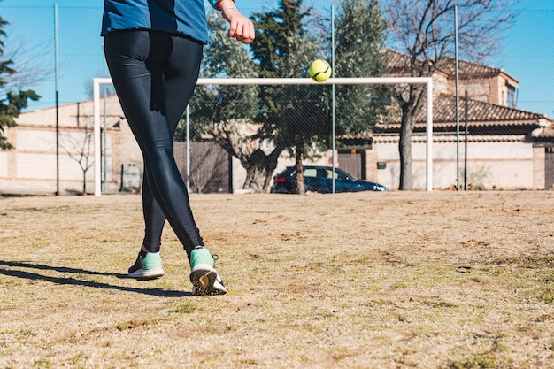 Mulher atirando um tiro livre em direção ao gol. campo de futebol de campo. conceito de futebol feminino.