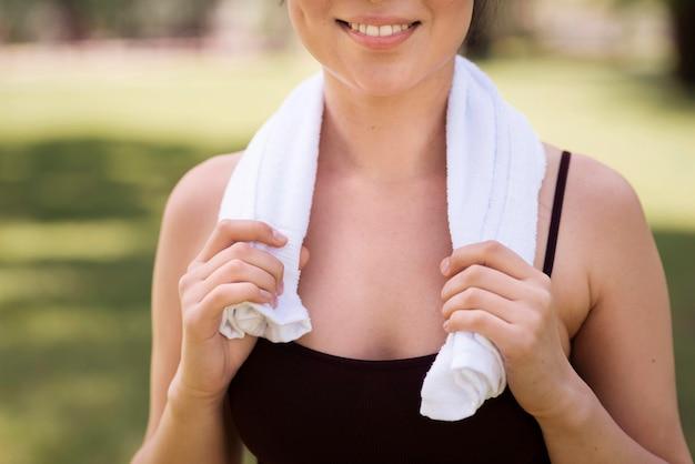 Mulher ativa close-up, segurando a toalha nos ombros