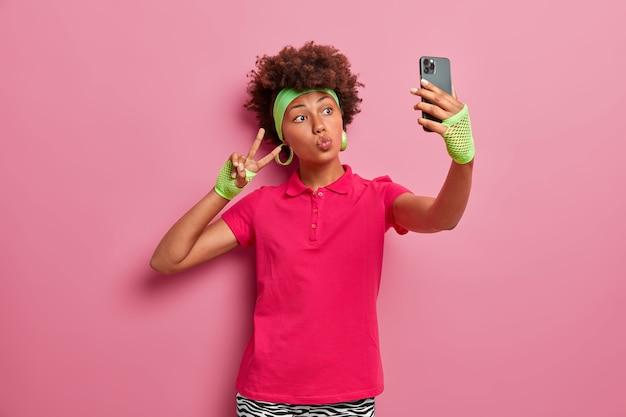 Mulher ativa de cabelos cacheados em camiseta rosa, tiara e luvas esportivas, tira selfie, faz gesto de vitória, segura telefone celular, sendo obcecada por poses de redes sociais internas