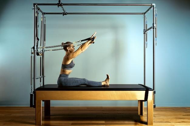 Mulher ativa e motivada faz exercícios de reformador de camas, beleza e saúde. plástico, postura, boa forma.