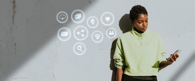 Mulher ativa em pé contra uma parede usando seu smartphone