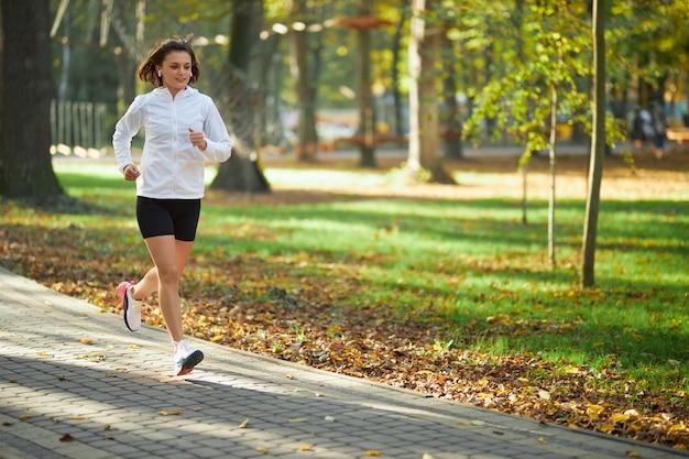 Mulher ativa em roupas esportivas correndo no parque