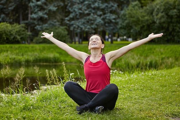 Mulher ativa está fazendo ioga em um parque público, perto da lagoa.