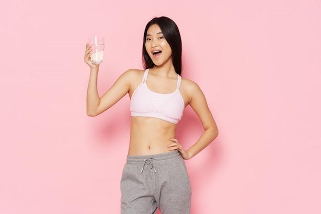 Mulher ativa, posando com um copo