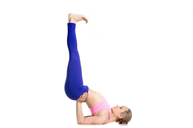 Mulher ativa que faz o exercício shoulderstand
