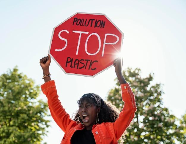 Mulher ativista segurando uma placa de pare, tiro médio