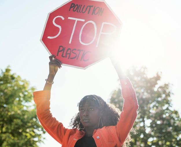 Mulher ativista segurando uma placa de pare