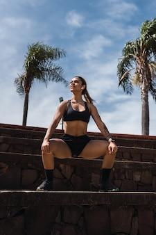 Mulher atleta alongamento antes de correr em um parque da cidade.