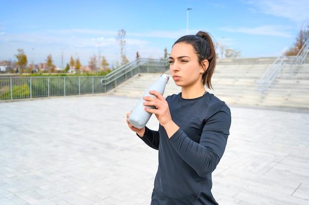 Mulher atleta bebendo água
