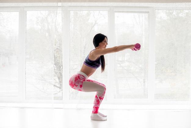 Mulher atleta de fitness realiza exercícios nas nádegas. musculação