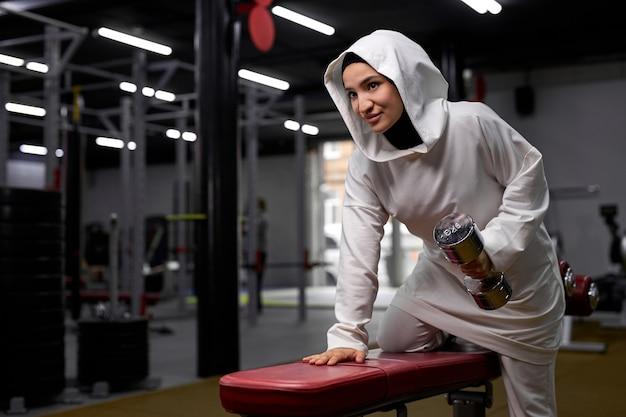 Mulher atleta em treinamento esportivo de hijab com halteres no moderno centro de fitness, jovem mulher muçulmana está cheia de energia e poder. motivação, estilo de vida saudável e conceito de esporte
