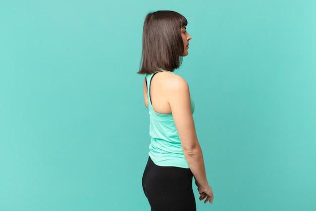 Mulher atleta em vista de perfil olhando para copiar o espaço à frente, pensando, imaginando ou sonhando acordada