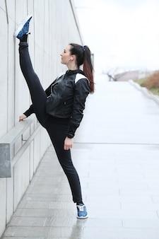 Mulher atleta fazendo alongamento na rua