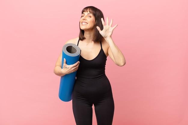 Mulher atleta sorrindo e parecendo amigável, mostrando o número cinco ou quinto com a mão para a frente, em contagem regressiva
