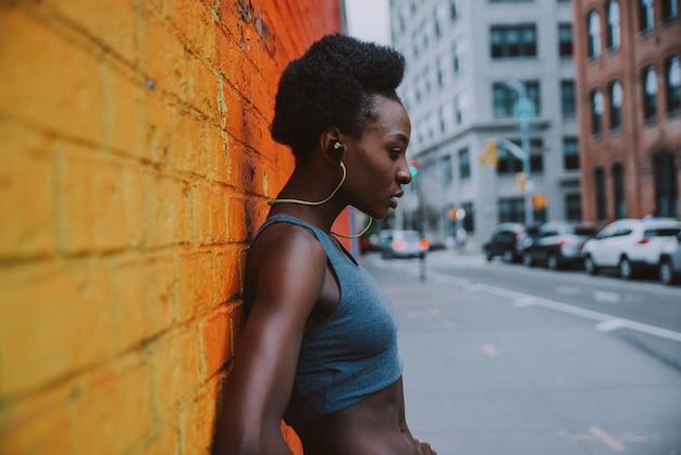 Mulher atleta treinando de manhã ao nascer do sol na cidade de nova york, brooklyn em segundo plano