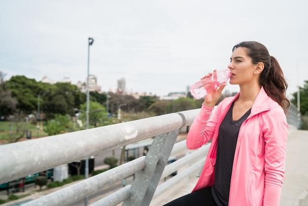 Mulher atlética água potável após o treino