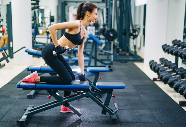 Mulher atlética bombeamento de músculos com halteres.