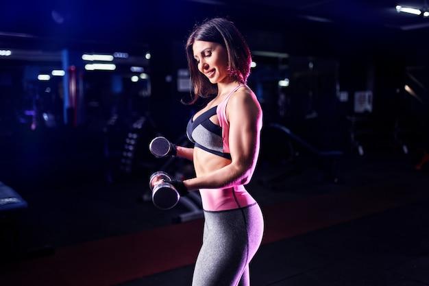 Mulher atlética brutal bombeando muscules com halteres