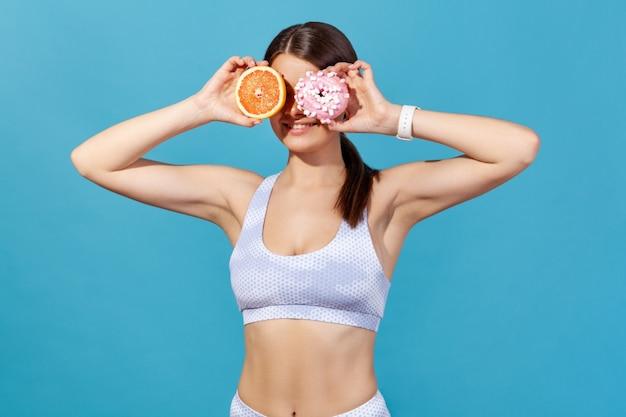 Mulher atlética cobrindo os olhos com toranja e donut