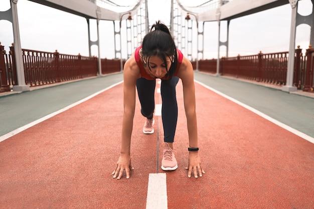 Mulher atlética com fones de ouvido sem fio se alongando antes de correr enquanto fica na ponte ao ar livre