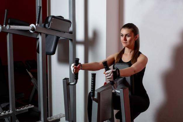 Mulher atlética concentrada fazendo exercícios na academia