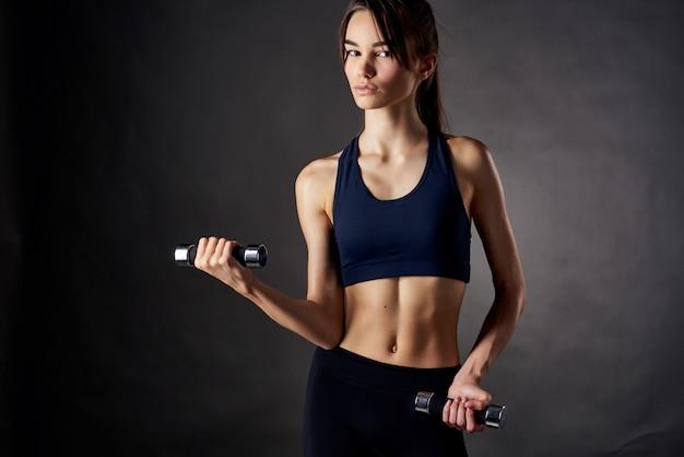 Mulher atlética corpo esguio exercício fitness dark foundation ginásio