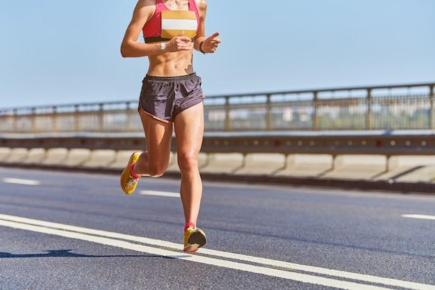 Mulher atlética correndo em roupas esportivas na cidade