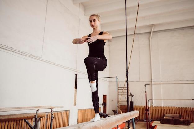 Mulher atlética de vista frontal treinando na trave de equilíbrio