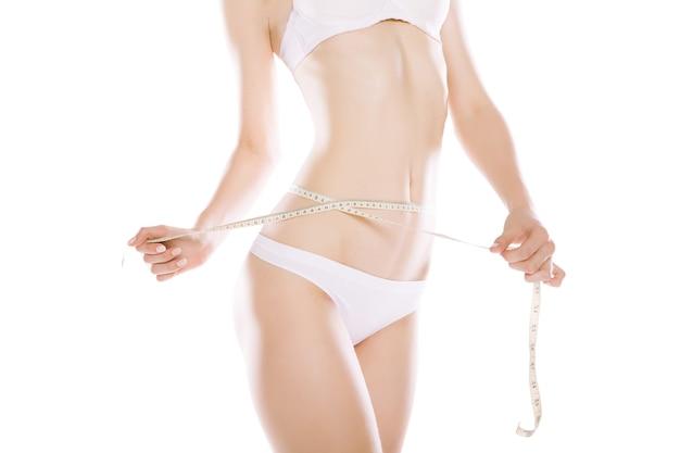 Mulher atlética e magra medindo a cintura com fita métrica após uma dieta isolada sobre fundo branco