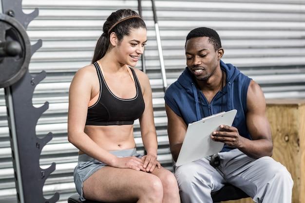 Mulher atlética e treinador sorrindo para a câmera no ginásio