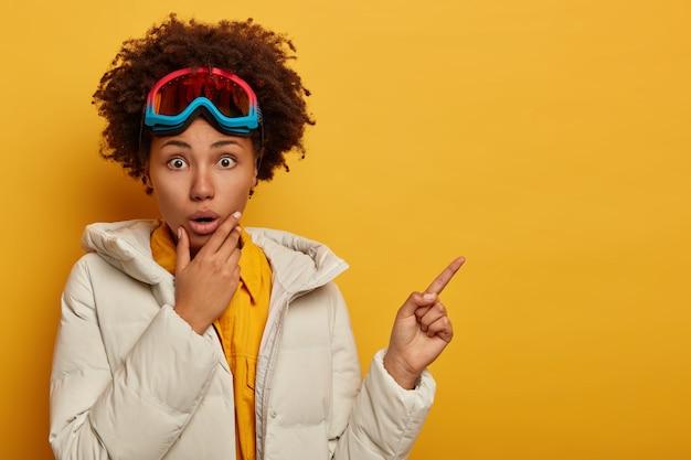 Mulher atlética em choque com cabelo encaracolado, aponta em um espaço em branco para seu conteúdo publicitário, mantém uma das mãos no queixo, em férias de inverno