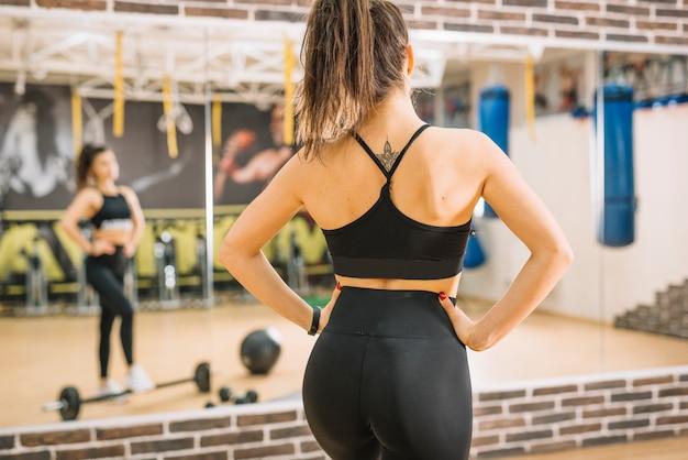 Mulher atlética em pé perto de halteres e espelhos