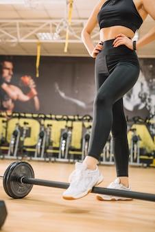 Mulher atlética em pé perto de halteres