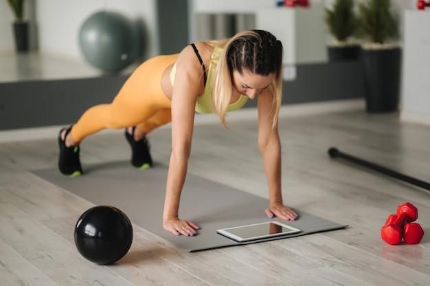 Mulher atlética em roupas esportivas faz exercícios em casa. mulher olha no tablet enquanto exercícios de diong.
