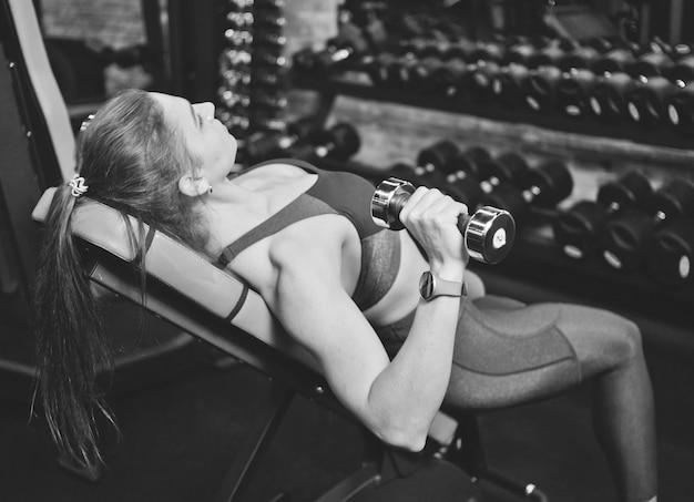 Mulher atlética em roupas esportivas fazendo halteres no banco inclinado na academia