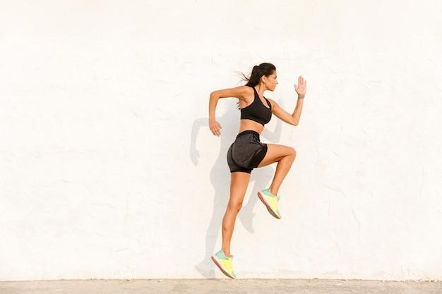 Mulher atlética em roupas esportivas, malhando e correndo