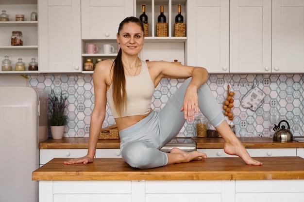 Mulher atlética em roupas esportivas, posando em cima da mesa. o conceito de beleza, saúde, nutrição adequada. mulher sorrindo e olhando para a câmera