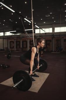 Mulher atlética exercitando-se em ginásio de treinamento funcional