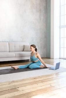 Mulher atlética fazendo esportes em casa fazendo ioga on-line usando um laptop