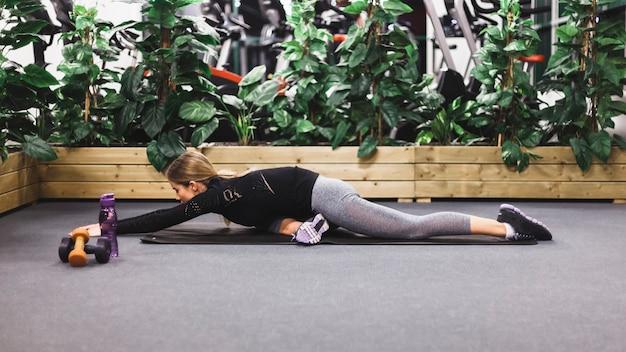 Mulher atlética fazendo exercícios de alongamento no tapete de ioga
