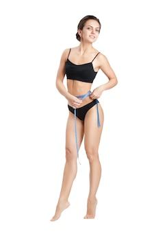 Mulher atlética feliz medindo sua cintura com fita métrica azul após uma dieta em um branco