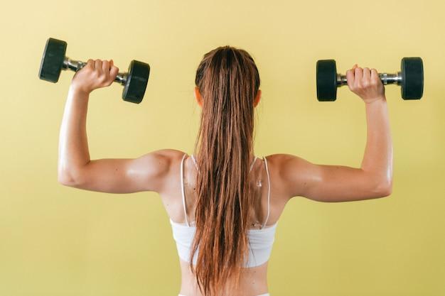 Mulher atlética fisiculturista com halteres. menina morena de cabelos longos com músculos levantando pesos na parede amarela