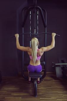 Mulher atlética forte e bonita treinando no ginásio