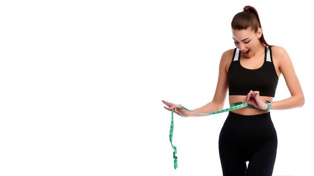 Mulher atlética forte e magra animada medindo abdômen em fundo branco isolado