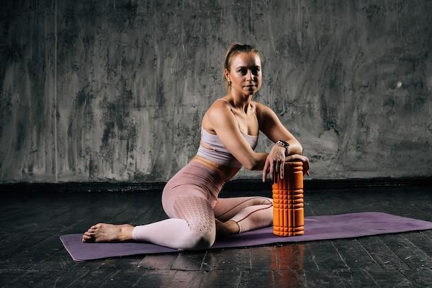 Mulher atlética jovem e musculosa com corpo bonito sentado com massageador de rolo de espuma na esteira de ioga.