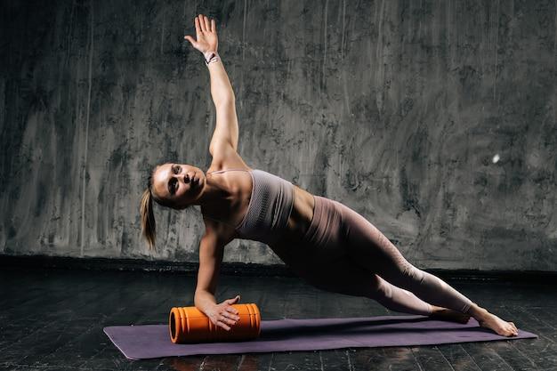 Mulher atlética jovem e musculosa com corpo lindo perfeito vestindo roupas esportivas, fazendo pose de prancha lateral usando massageador de rolo de espuma na esteira de ioga. mulher caucasiana de fitness posando no estúdio.